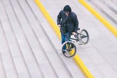 Den stilfulla BMX-cykeltonåringen stiger ned ner trappan Gå med en cykel BMX-kultur fotografering för bildbyråer