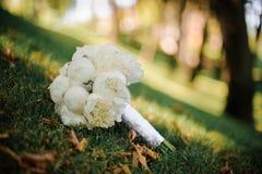 Den stilfulla bröllopbuketten av vita pioner ligger på det gröna gräset royaltyfri fotografi