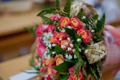 Den stilfulla buketten av röda rosor och det röda bandet i en rund svart ask nära den rosa gåvan hänger löst Valentin och årsdagb Royaltyfria Bilder
