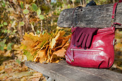 Den stilfulla burgundy skuldrapåsen och handskar av samma färgar på vara Arkivbilder