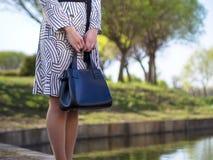 Den stilfulla europeiska unga kvinnan i en regnrock, strumpbyxor, skor med häl, med en svart piskar påsen i hennes händer i parke royaltyfri bild