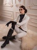 Den stilfulla flickan i en dräktryttare poserar Royaltyfri Fotografi