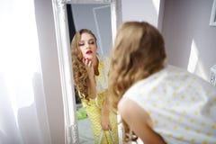 Den stilfulla flickan ser i spegeln royaltyfria foton