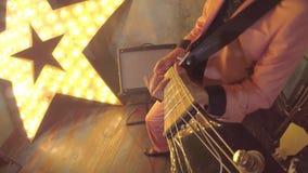 Den stilfulla gitarrspelaren vaggar solo eller rytm för stil för musik för disko för stjärnalekar skraj på den elektriska gitarre stock video