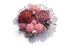 Den stilfulla handgjorda broschen som består av rosa färger, blommar från tyg på en vit bakgrund Arkivbild