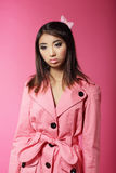 Den stilfulla japanska flickan i rosa färger Outwear över kulör bakgrund Arkivfoton