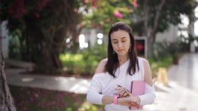 Den stilfulla kvinnan som rymmer hennes minnestavlaPC, väntar i parkera stock video