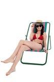 Den stilfulla kvinnliga bikinin modellerar att koppla av i kanfasstol Arkivbilder