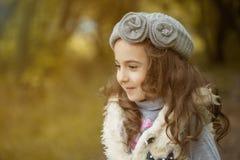 Den stilfulla lockiga lilla brunetten som in poserar, parkerar Royaltyfri Bild