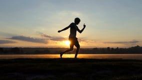 Den stilfulla mannen dansar fri stil på en sjöbank på solnedgången i slo-mo arkivfilmer