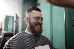 Den stilfulla mannen med ett skägg sitter och ler på en barberare shoppar Barberaren i svarta handskar gör bespruta för frisyr arkivbild