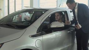 Den stilfulla mannen talar med representanten och kontrollerar kabinen för bil` s i bilåterförsäljare arkivfilmer
