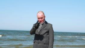 Den stilfulla manvisningen går med mig tecknet och att blinka för gest Elegant och säker ung affärsman på stranden Aff?r stock video