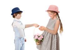 Den stilfulla pojken ger en flickakorg av blommor Arkivbild