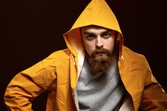 Den stilfulla rödhåriga grabben med ett iklädda skägg och mustasch en grå t-skjorta och ett gult omslag med en huv poserar p royaltyfria foton