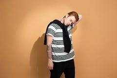 Den stilfulla r?dh?riga grabben i en randig skjorta med tatueringen p? hans hand poserar med den svarta tr?jan p? hans skuldror p arkivbild