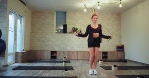 Den stilfulla sportiga kvinnan med en fi-muskelkropp som hoppar på ett rep i en stor rymlig aerobisk studio koncentrerade mycket, arkivfilmer