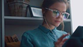 Den stilfulla studentflickan sitter vid fönstret och läser en eBook stock video