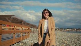 Den stilfulla tonåriga flickan hoppar på den tomma stranden i soligt väder som i huvudsak ler stock video