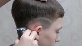 Den stilfulla tonårs- frisyren i barberaren shoppar En yrkesmässig manlig frisör rakar en remsa ovanför örat för grabb` s med en  arkivfilmer