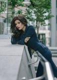 Den stilfulla trendiga sexiga brunetten i blått passar i staden bedsheetmode lägger förföriskt vitt kvinnabarn för foto Arkivfoto