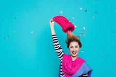 Den stilfulla unga kvinnan tar bort en stucken rosa hatt från hennes huvud i studion på en blå bakgrund Vinterfarväl kommer fjäde Royaltyfri Fotografi