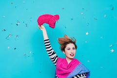 Den stilfulla unga kvinnan tar bort en stucken rosa hatt från hennes huvud i studion på en blå bakgrund Vinterfarväl kommer fjäde Royaltyfria Bilder