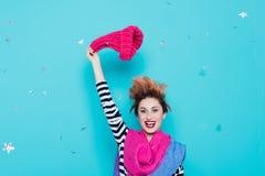 Den stilfulla unga kvinnan tar bort en stucken rosa hatt från hennes huvud i studion på en blå bakgrund Vinterfarväl kommer fjäde Arkivfoto