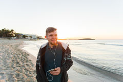 Den stilfulla unga mannen lyssnar till musik i hörlurar på en smartphone på stranden Livsstil, teknologi och folkbegrepp royaltyfri foto