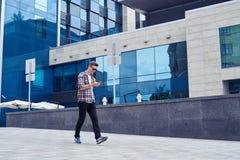 Den stilfulla unga mannen lyssnar till musik och tycker om stadspanorama Royaltyfri Fotografi