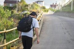 Den stilfulla unga mannen med en ryggsäck går bara på en bergväg royaltyfri fotografi