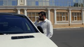 Den stilfulla unga mannen med ett skägg i en vit skjorta och mörka exponeringsglas står nära hans vita bil och talar på telefonen arkivfilmer