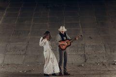 Den stilfulla zigenska kvinnan i boho beklär att dansa nära stilig man, c Royaltyfri Foto
