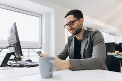 Den stiliga affärsmannen använder en smartphone och ler, medan arbeta i regeringsställning royaltyfri bild
