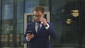 Den stiliga affärsmannen använder smartphoneanseende på kontorsbyggnadbakgrund stock video
