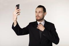 Den stiliga affärsmannen i svart dräkt gör fotoet genom att använda telefonen royaltyfri foto