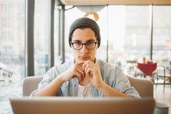 Den stiliga affärsmannen i tillfälliga kläder och glasögon använder en bärbar dator i kafé fotografering för bildbyråer