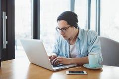 Den stiliga affärsmannen i tillfälliga kläder och glasögon använder en bärbar dator i kafé royaltyfri foto
