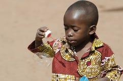 Den stiliga afrikanen behandla som ett barn pojken som har rolig det fria med såpbubblor Arkivbilder