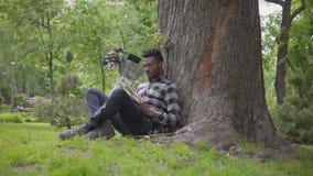 Den stiliga afrikansk amerikanmannen som sitter n?ra hans cykel under ett gammalt tr?d i, parkerar att l?sa en bok Fritid utomhus stock video
