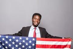 Den stiliga afro- amerikanska mannen i klassisk dräkt ser kameran och ler att stå med amerikanska flaggan Royaltyfria Bilder