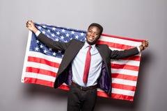 Den stiliga afro- amerikanska mannen i klassisk dräkt ser kameran och ler att stå med amerikanska flaggan Royaltyfri Bild