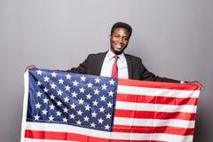 Den stiliga afro- amerikanska mannen i klassisk dräkt ser kameran och ler att stå med amerikanska flaggan Arkivbild
