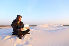 Den stiliga arabiska manliga arkitekten ser dokument och sitter på sa Royaltyfria Bilder