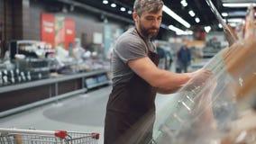 Den stiliga arbetaren av stormarknaden tar munkar från shoppingvagnen och sätter dem i behållare på hyllor in arkivfilmer