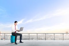 Den stiliga asiatiska affärsmannen som sitter på den blåa resväskan, rymmer bärbara datorn och att arbeta på modern terrass royaltyfria bilder