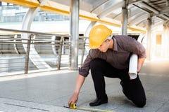 Den stiliga asiatiska arbetar- eller teknikermannen mäter golvet förbi royaltyfri fotografi