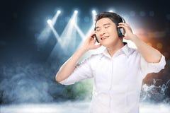 Den stiliga asiatiska mannen i den vita skjortan med hörlurar tycker om musiken royaltyfri bild