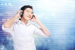 Den stiliga asiatiska mannen i den vita skjortan med hörlurar tycker om musiken royaltyfri fotografi