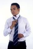 Den stiliga attraktiva unga asiatiska affärsmandressingen, fixande hans band och ordnar till för att arbeta Royaltyfri Bild